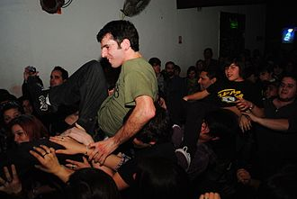 "Moshing - A crowd of moshers, with a few people ""crowdsurfing"" on top of the mosh pit."