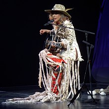Gaga wearing a white dress, red boots and a hat, playing guitar onstage