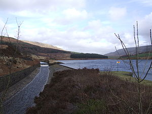 Longdendale Chain - At the Rhodeswood reservoir dam, we see the outflow canal from the Torside Reservoir dam, alongside the Rhodeswood Reservoir. The Torside dam  can be seen in the distance. To the right is Shining Clough Moss and Bleaklow. To the left Bareholm Moss and Black Hill