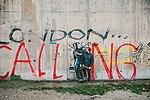Meme artist XVALA standing near graffiti artist Banksy's Steve Jobs Mural in Calais, France 2017.jpg