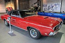 Vue de trois quarts avant droit, voiture rouge à toit noir, dans une salle d'exposition. Porte-skis à l'arrière.