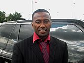 A smiling black man dressed in suit and tie stands by a large shiny car.