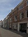 foto van Dwarshuis met geverfde gevel, afgesloten door gootlijst op klossen