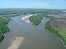 Widok z lotu ptaka brązowawej rzeki przez dolinę rolniczą
