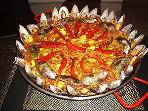 A mixed, red paella garnished with red bell pe...