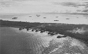A peninsula with eight ships beached on the shore in the foreground and over eleven ships anchored off the opposite shore. Smoke is rising from the peninsula.