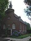 foto van Eenvoudig, driezijdig gesloten bakstenen zaalkerkje uit 1810, gelegen aan de voet van de dijk, met aan de zuid- en zuidwestzijde een verhoogd aangelegd kerkhof