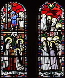 Church stained-glass window depicting the martyrdom of a line of nuns