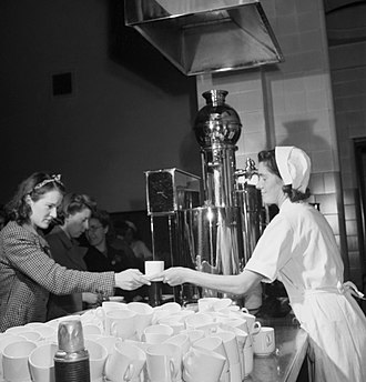 Tea lady - An English woman, working as a part-time tea lady, serves tea to a female worker at an aircraft factory in Bristol, 1942