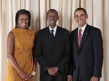 Michelle Obama, Paul Kagame and Barack Obama, standing and smiling in front of a curtain