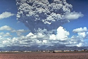A tower of grey ash erupts above a mountain
