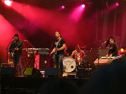 The band performing live, August 25, 2005 in Paris, France. Included in this performance are two bandmates from the band Eleven, Alain Johannes and the late Natasha Shneider, who joined the line-up for Lullabies to Paralyze and the supporting tour QOTSA Live Paris 200508 2.jpg