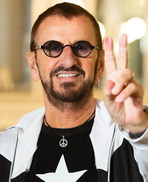 A colour photograph of Starr doing a peace sign wearing sunglasses and a black T-shirt.