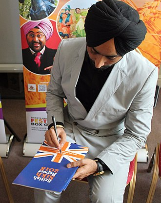British Sikh Report - Satinder Sartaaj the famous singer of Sufi songs signing a copy of the British Sikh Report