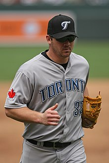 "A man wearing a gray baseball uniform with ""Toronto"" across the chest and a black baseball cap"