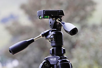 Tripod head - A 3-way pan-tilt head on a tripod, showing panoramic rotation, lateral tilt, and front tilt controls