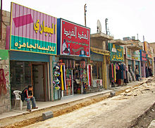 Stores with signs in large Arabic lettering stretching from the lef foreground to the right rear on a street where reconstruction work is in progress