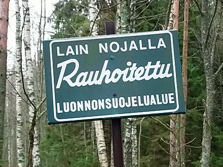 "A conservation area's sign in the Finnish forest. It says, ""A conservation area protected by law""."