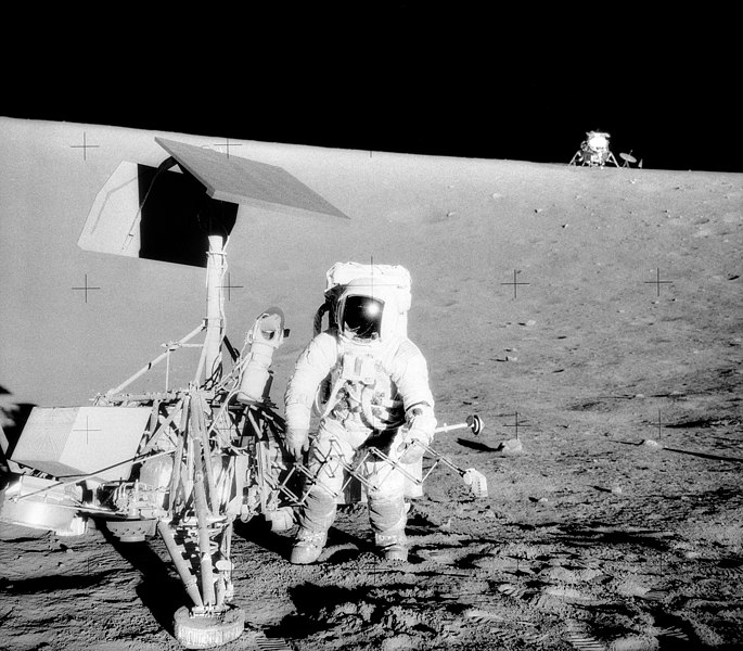 "Charles Conrad Jr., Apollo 12 Commander, examines the unmanned Surveyor III spacecraft during the second extravehicular activity (EVA-2). The Lunar Module (LM) ""Intrepid"" is in the right backgroun"
