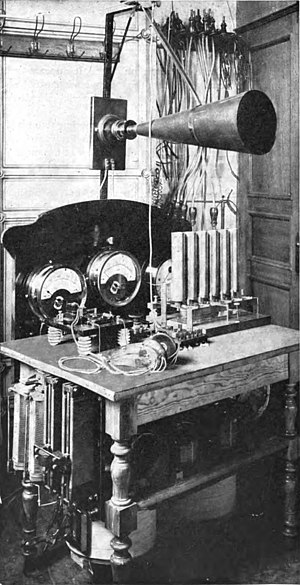 Amplitude modulation - One of the crude pre-vacuum tube AM transmitters, a Telefunken arc transmitter from 1906.  The carrier wave is generated by 6 electric arcs in the vertical tubes, connected to a tuned circuit.  Modulation is done by the large carbon microphone (cone shape) in the antenna lead.
