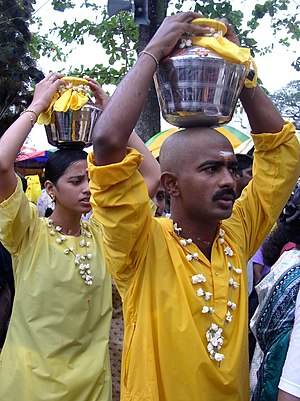 Worshippers carry heavy pots in a procession d...