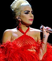 A blonde woman wearing a red dress singing into a microphone.