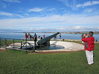 Tourists inspecting a disappearing gun at North Head, New Zealand