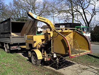 Woodchipper - A portable woodchipper and truck with wood chips collected in the truck bed.