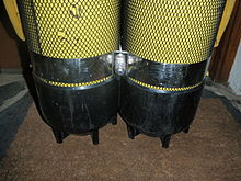 The lower part of a twin steel set showing a stainless steel tank band just above the black plastic cylinder boots. The boots and tank band have been fitted over close fitting small mesh netting covers intended to protect the paintwork and facilitate rinsing and drying of the surface under the boots.