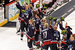 Several women wearing blue hockey jerseys wave to a crowd.