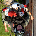 US Navy 050907-N-5345W-049 U.S. Navy Aviation Warfare Systems Operator 1st Class Robert Webber keeps a firm grip on a New Orleans resident as he is hoisted-up during mandatory evacuation efforts.jpg