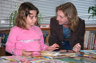Teaching assistant - A teaching assistant interacts with a reading child