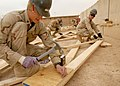 US Navy 080207-N-0553R-006 Builder 3rd Class Steven Deboard and other Seabees assigned to Naval Mobile Construction Battalion (NMCB) 1 make trusses to rebuild a chapel that was destroyed by an electrical fire.jpg