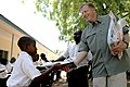 US Navy 091102-N-2420K-101 Boatswain's Mate 1st Class Brian Shapley, from Canadensis, Pa. deployed with Maritime Civil Affairs Team (MCAT) 214, hands a packet of school supplies to a child at the Tongoni Primary School in Tanga.jpg