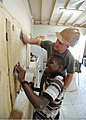 US Navy 110417-N-NY820-518 Sgt. Peter Swigart, from Maumee, Ohio, and a local child sand newly built cabinets at Trenchtown Primary School in Kings.jpg