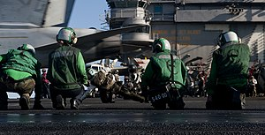 US Navy 120101-N-OY799-075 Sailors observe as a final checker signals safe for launching an F-A-18E Super Hornet from the Tophatters of Strike Figh.jpg