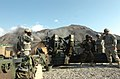 US soldiers cover ears while Afghan National Army soldier fires M-198 howitzer.jpg