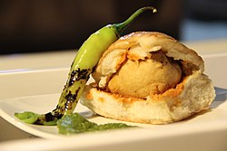 A plate of vada pav with seasoning of red chilli powder and a green chilli.