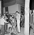 Verkoper (kind) en klanten bij op de grond uitgestalde feestartikelen, Bestanddeelnr 255-1930.jpg
