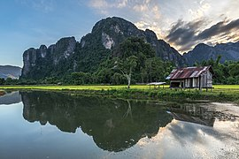 Water reflection of karst mountains, wooden hut, trees and colorful clouds at sunset with green paddy fields, Vang Vieng, Laos.jpg