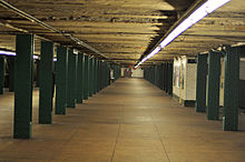 The mezzanine at West Fourth Street station in Greenwich Village. Several support beams, painted green can be seen throughout the mezzanine. On the ceiling, a long and straight white light can be seen.