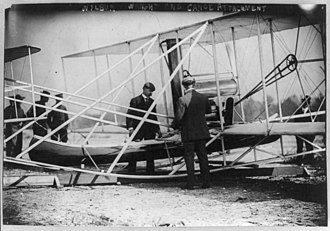 Charlie Taylor (mechanic) - Charlie and Wilbur attach a canoe onto a new Flyer at Governor's Island New York, October 1909.
