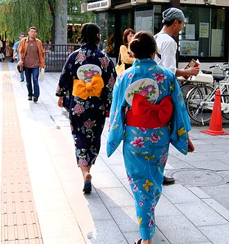 Yukata - Women in yukata, from behind to show the obi and fans, in Tokyo, Japan