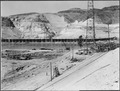 """""""View from east tailrace slope - east and center conveyor suspension bridge towers - cofferdam, and in center of... - NARA - 293978.tif"""