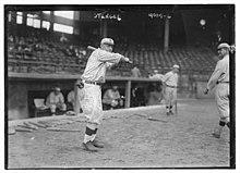 Muž v staromódní baseballu uniformě drží pálku nad rameno, levák