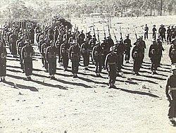 A black and white photograph of soldiers on a unsealed parade ground in a rural setting, wearing battledress uniforms, with slouch hats, webbing and rifles.