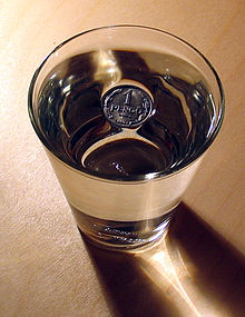 """Photo of a drinking glass filled with water from above.  In the middle of the water surface there is a metal coin that is labeled """"1 Pfennig"""".  Around the coin you can see that the surface of the water is dented where it touches the coin."""