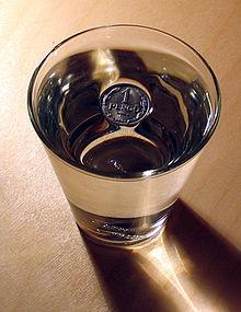 """Foto eines mit Wasser gefüllten Trinkglases von oben. In der Mitte der Wasserfläche schwimmt eine Münze aus Metall, die mit """"1 Pfennig"""" beschriftet ist. Rund um die Münze ist zu erkennen, dass die Wasseroberfläche dort eingedellt ist, wo sie die Müne berührt."""