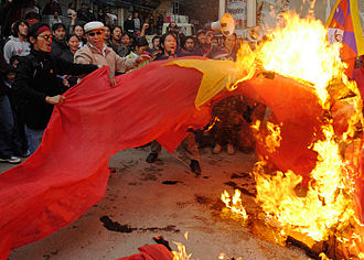 Flag desecration - Protesters burn a People's Republic of China flag in Tibet.