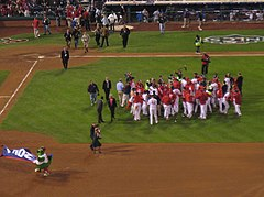 A group of men in red and white baseball uniforms gather on a baseball field.
